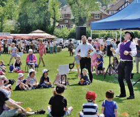 Entertainer watched by seated children on sunny day
